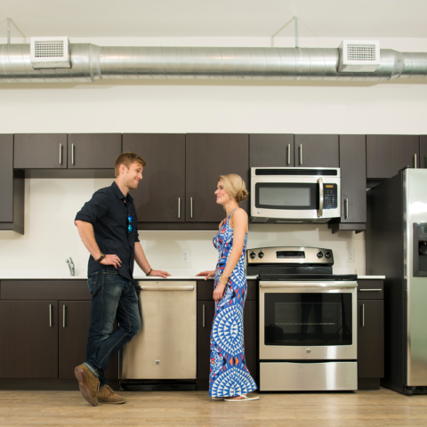 Residents in spacious kitchen with stainless steel appliances in Downtown Wilmington apartment